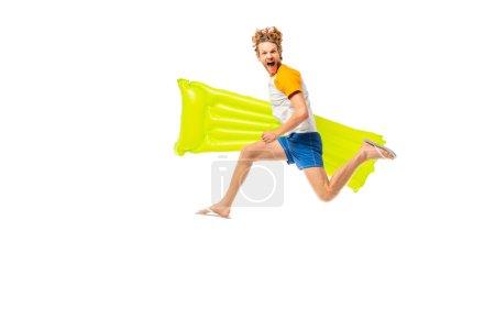 Foto de Vista lateral del hombre excitado sosteniendo el colchón inflable mientras que salta aislado en blanco - Imagen libre de derechos