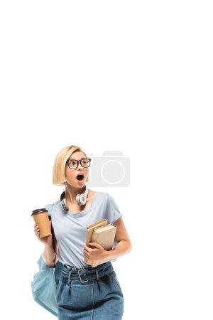 Photo pour Choqué étudiant tenant café pour aller et des livres isolés sur blanc - image libre de droit