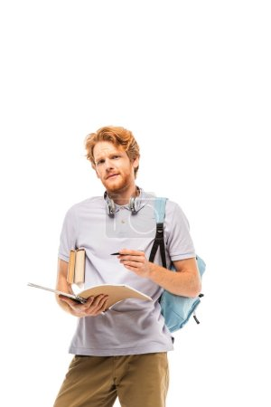 Student mit Rucksack hält Notizbuch und Stift in der Hand, während er die Kamera isoliert auf Weiß betrachtet