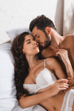 Photo for Muscular man lying near seductive girlfriend with closed eyes on bed - Royalty Free Image