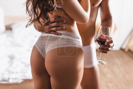 Cropped view of shirtless man in underpants holding glass of wine and hugging girlfriend in lace panties in bedroom