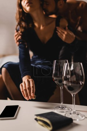 Photo for Cropped view of woman putting wedding ring near smartphone and glasses of wine on coffee table while sitting beside man on bed - Royalty Free Image