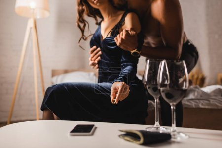 Photo for Cropped view of shirtless man taking off dress from woman holding wedding ring near smartphone and glasses of wine on coffee table - Royalty Free Image