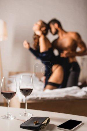Foto de Enfoque selectivo de anillo de boda en la cartera cerca de copas de vino y teléfono inteligente en la mesa de café con sexy pareja en la cama en el fondo - Imagen libre de derechos