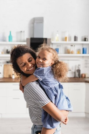 Photo pour African american girl looking at camera and embracing mother holding her on hands in kitchen - image libre de droit