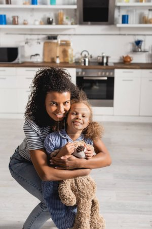 Photo for Young african american woman embracing excited daughter with teddy bear while looking at camera in kitchen - Royalty Free Image