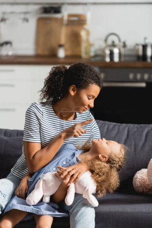 young african american mother in striped t-shirt having fun with daughter while sitting on sofa in kitchen