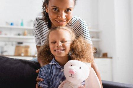 junge afrikanisch-amerikanische Mutter blickt in die Kamera nahe aufgeregter Tochter mit geschlossenen Augen, die Spielzeughasen hält
