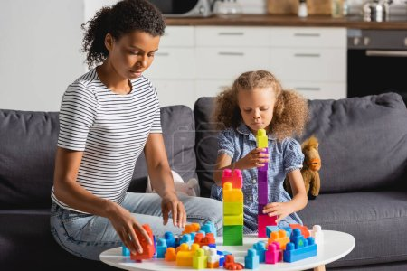 young african american babysitter and girl playing with colorful building blocks while sitting on sofa