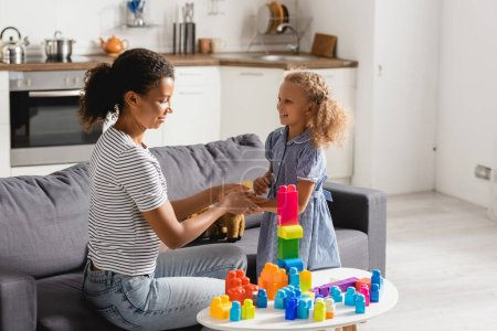 young african american nanny touching hand of girl near table with colorful building blocks