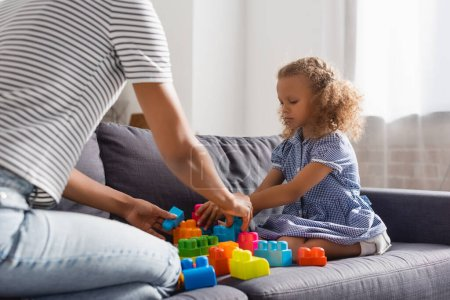 partial view of babysitter and african american girl playing with colorful building blocks on couch