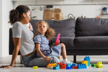 african american babysitter and girl looking at each other while sitting on floor near multicolored building blocks