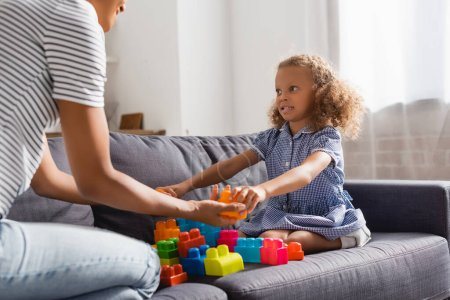 partial view of nanny giving building blocks to african american girl while playing on sofa