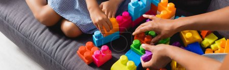 Photo for Cropped view of african american babysitter and girl playing with multicolored building blocks, panoramic shot - Royalty Free Image