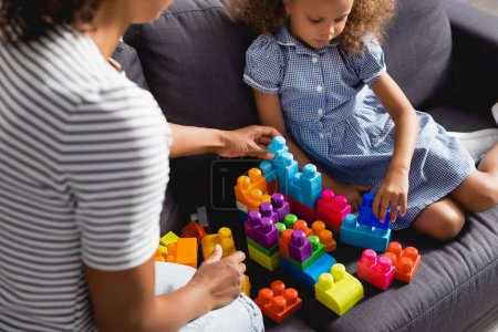Photo pour Cropped view of babysitter near african american girl in dress playing with multicolored building blocks - image libre de droit