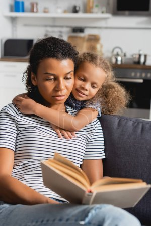 selective focus of african american girl embracing nanny in striped t-shirt reading book on couch