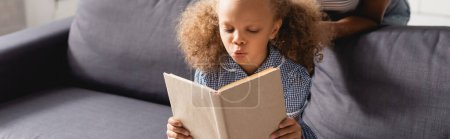 cropped view of nanny behind focused african american girl sitting on sofa and reading book, website header