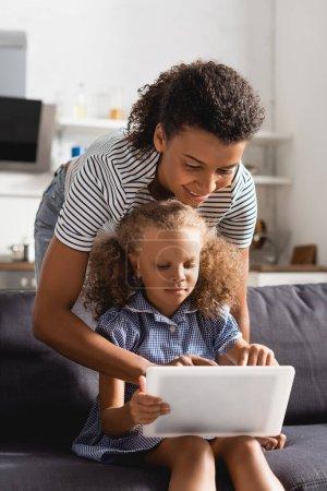 Photo pour Jeune baby-sitter afro-américaine utilisant une tablette numérique avec une fille assise sur le canapé - image libre de droit