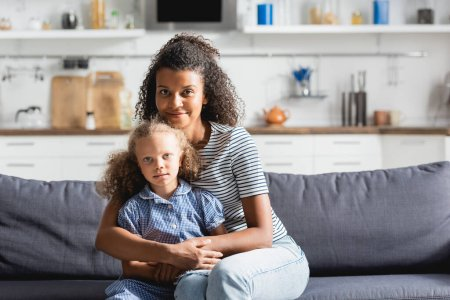Photo for Young african american woman embracing daughter and looking at camera while sitting on couch in kitchen - Royalty Free Image