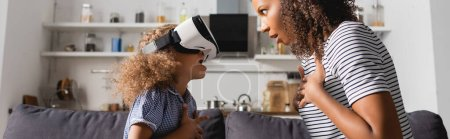 Photo for Excited african american babysitter and child in vr headset holding hands on chests while looking at each other, panoramic shot - Royalty Free Image
