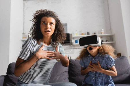 Photo for Excited african american nanny and girl in vr headset holding hands on chests while sitting with open mouths - Royalty Free Image