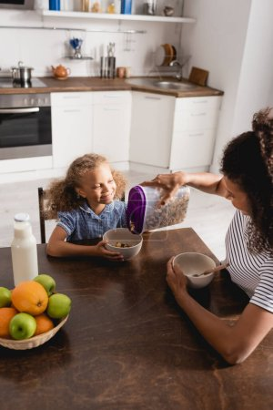 Photo for High angle view of african american woman pouring cornflakes into bowl near daughter, fresh fruits and milk - Royalty Free Image