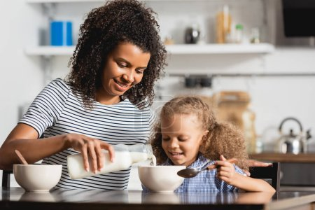 young african american mother in striped t-shirt pouring milk into bowl near daughter holding spoon