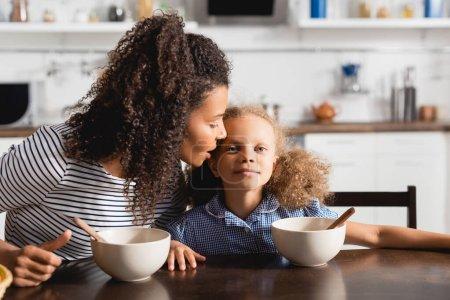 Photo pour Femme afro-américaine en t-shirt rayé chuchotant à l'oreille de sa fille pendant le petit déjeuner - image libre de droit
