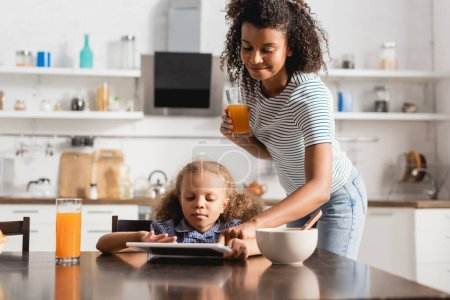 Photo for African american mother holding orange juice and touching digital tablet near concentrated child in kitchen - Royalty Free Image