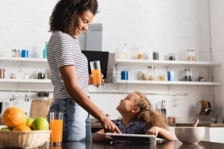 Photo pour Jeune femme afro-américaine tenant du jus d'orange et touchant tablette numérique près de la fille dans la cuisine - image libre de droit