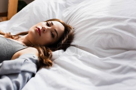 selective focus of depressed woman lying on bed and looking at camera