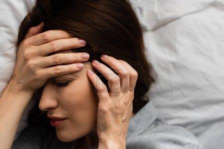 vista superior de la mujer morena que sufre de dolor y tocando la cabeza en el dormitorio