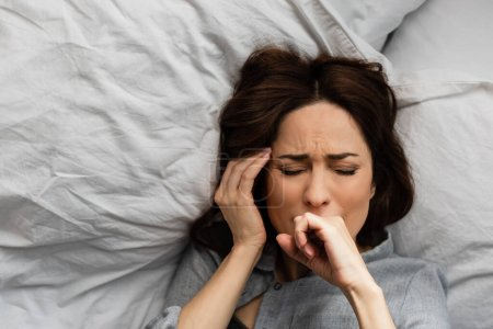 vista superior de la mujer cansada que sufre de dolor y tocando la cabeza mientras está acostada en la cama