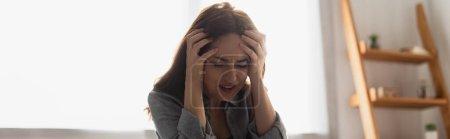 Photo pour Récolte panoramique de femme brune avec les yeux fermés souffrant de douleur et touchant la tête à la maison - image libre de droit