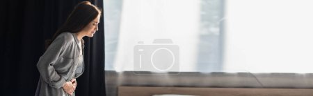 Photo for Panoramic concept of brunette woman suffering from stomach ache in bedroom - Royalty Free Image
