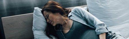 plano panorámico de la mujer embarazada que sufre de dolor en la cama