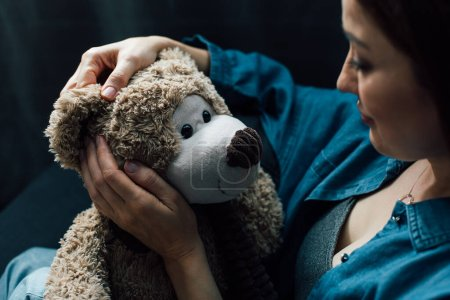 selective focus of depressed woman holding teddy bear