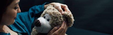 image horizontale d'une femme déprimée tenant un ours en peluche