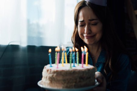 Photo pour Selective focus of sad woman crying while holding birthday cake with candles - image libre de droit