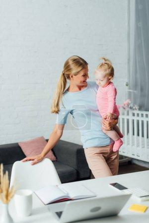 Photo pour Concentration sélective de la mère tenant bébé fille près de gadgets et bloc-notes sur la table à la maison - image libre de droit