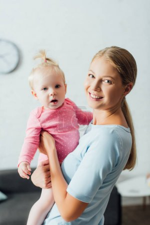 Photo for Woman looking at camera while holding baby daughter at home - Royalty Free Image