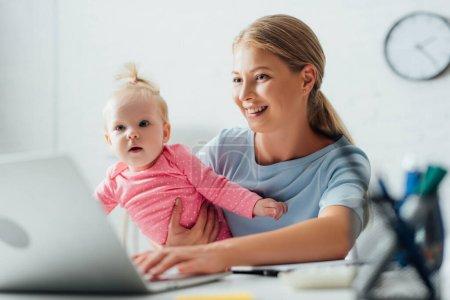 Photo pour Concentration sélective de la mère tenant bébé fille et utilisant un ordinateur portable à la maison - image libre de droit
