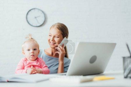 Enfoque selectivo de la mujer hablando en el teléfono inteligente mientras trabaja cerca de la hija bebé en casa