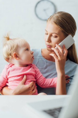 Selective focus of woman talking on smartphone and looking at infant daughter near laptop on table