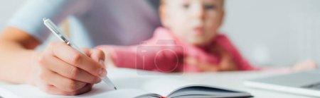 Photo pour Récolte panoramique de femme écrivant sur un carnet près d'une petite fille à la maison - image libre de droit