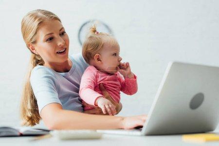 Photo pour Concentration sélective de la mère tenant bébé fille tout en travaillant sur un ordinateur portable à la maison - image libre de droit