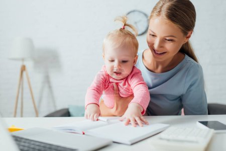 Photo pour Concentration sélective du cahier tactile du nourrisson près de la mère et des gadgets sur la table - image libre de droit
