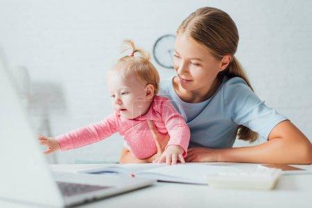 Photo pour Concentration sélective de la femme tenant bébé fille sur les mains près du portable et des gadgets sur la table - image libre de droit