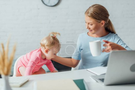 Photo for Selective focus of woman holding cup and touching baby girl near laptop and stationery on table - Royalty Free Image