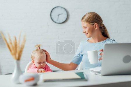 Photo pour Mise au point sélective de pigiste avec tasse touchant la petite fille près de l'ordinateur portable et la papeterie sur la table - image libre de droit